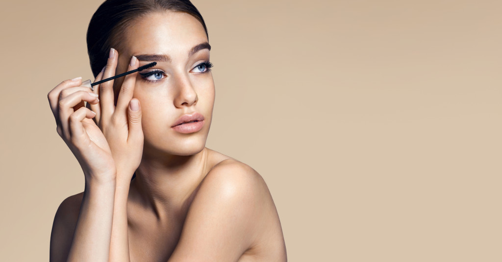 Mascara applying. Makeup closeup. Eyes make-up / photos of appealing brunette girl on beige background