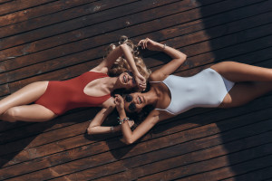 Top view of two attractive young women in swimwear smiling while lying down outdoors